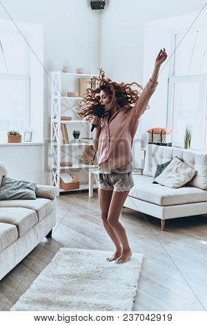 Rock star. Full length of attractive young women singing using comb and smiling while dancing at home stock photo