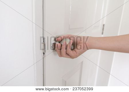 Close-up young woman handle stainless door knob, Women are opening door,Close up door knob stock photo
