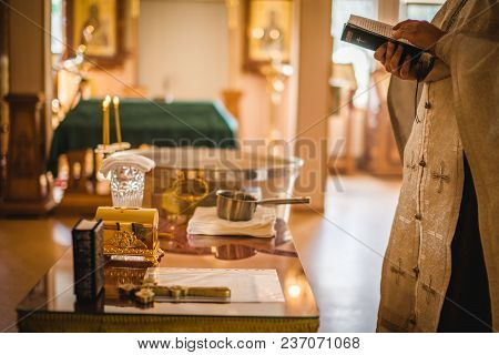 Beautiful Golden Cross In Male Hands Of Priest Wearing Gold Robe On Ceremony In Christian Cathedral