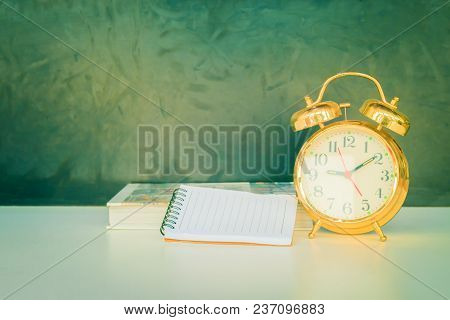 alarm clock old vintage gold and book over white on black background. with copy space add text. color cinematic Vintage style tone stock photo