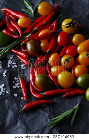 Multicolored piquant cherry tomatoes and chili peppers on a black background. Close-up. stock photo