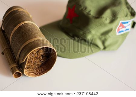 Some Cuban cigars rolled in banana leaf and military cap on the background stock photo