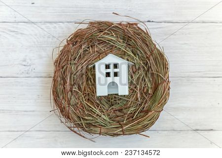 Miniature white toy model house rests in nest on rustic old vintage white wooden background. Eco village environmental real estate mortgage property insurance dream home ecology investment concept stock photo