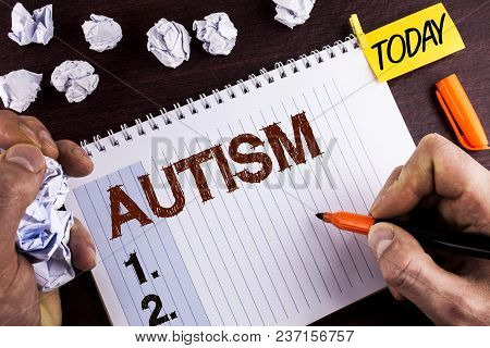 Word writing text Autism. Business concept for Autism Awareness conducted by social committee around the globe written by Man Notepad wooden background holding Marker Today Paper Balls. stock photo