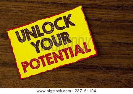 Handwriting text writing Unlock Your Potential. Concept meaning Reveal talent Develop abilities Show personal skills written Yellow Sticky note paper the wooden background. stock photo