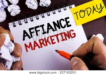 Handwriting text Affiance Marketing. Concept meaning joining two or more companies in same field mutual goal written by Man Notepad wooden background Today Paper Balls. stock photo