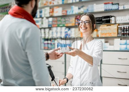 Young Woman Pharmacist Giving Medications To The Male Client Standing At The Paydesk Of The Pharmacy