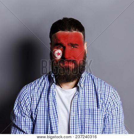 Face of young bearded man painted with flag of Tunis. Football or soccer team fan, sport event, faceart and patriotism concept. Studio shot at gray background, copy space stock photo
