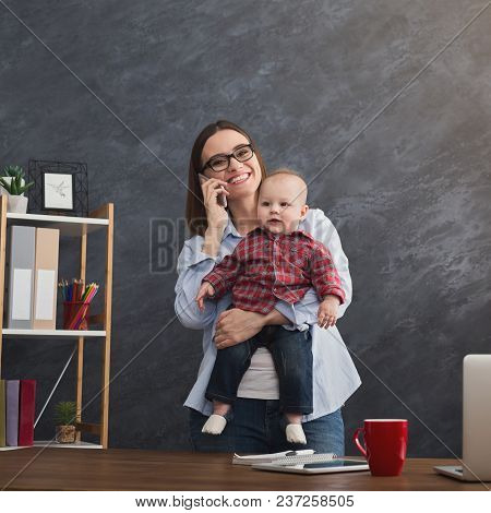 Happy mother working at office with her baby. Young woman talking on phone and using laptop while spending time with her child. Business, motherhood, multitasking and family concept, crop stock photo