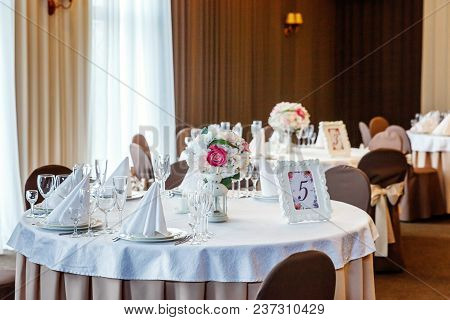 Glasses, flowers, fork, knife, napkin folded in a pyramid, served for dinner in restaurant with cozy interior. Wedding decorations and items for food, arranged by the catering service on a large table covered with white tablecloth stock photo