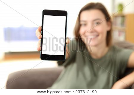 Happy teen showing a blank smart phone screen sitting on a couch in the living room at home stock photo