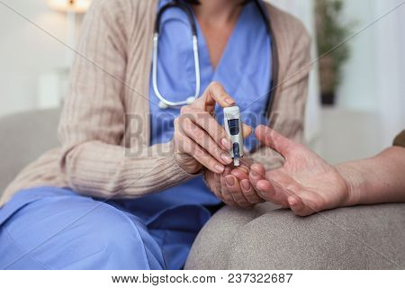Blood sugar. Close up of female tender hands using blood glucose meter while taking blood sample stock photo
