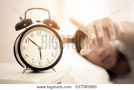 Man hand reaching out to alarm clock for snooze stock photo
