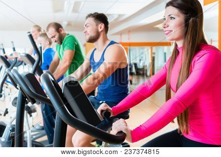 Male and female athletes doing spinning on home trainers in health club gym stock photo