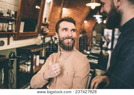 Another picture of happy customer is looking at the hairdresser and smiling. He is satisfied with the result. He is showing his big thumb up to the hairstylist stock photo