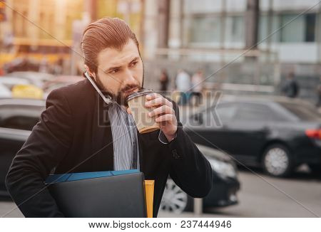 Busy man is in a hurry, he does not have time, he is going to eat snack on the go. Worker eating, drinking coffee, talking on the phone, at the same time. Businessman doing multiple tasks. Multitasking business person stock photo