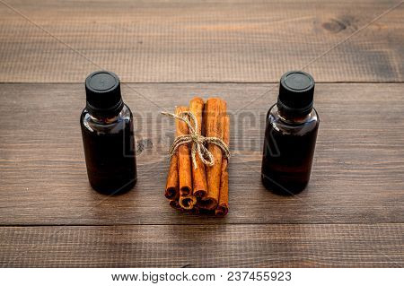 Cinnamon oil for cooking, aromatheraphy, skin care. Bottles near cinnamon sticks on dark wooden background. stock photo