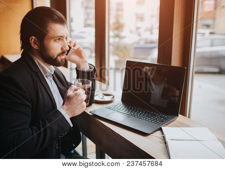 Busy man is in a hurry, he does not have time, he is going to eat snack on the go. Worker eating, drinking coffee, talking on the phone, at the same time. Businessman doing multiple tasks. Multitasking business person. stock photo