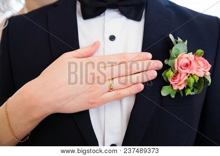 Wedding boutonniere on suit of groom and hand of bride stock photo