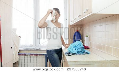 Housewife holding soiled smelly sock in laundry room stock photo