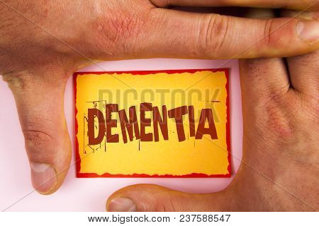 Word writing text Dementia. Business concept for Long term memory loss sign and symptoms made me retire sooner written Yellow Sticky note paper between Hands plain background. stock photo