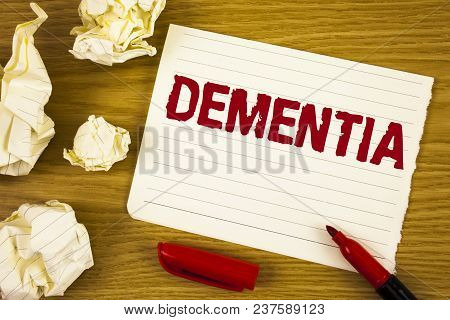 Word writing text Dementia. Business concept for Long term memory loss sign and symptoms made me retire sooner written Tear Notepad paper wooden background Marker Paper Balls next to it stock photo