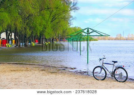 Lonely bicycle standing on beach during flooding on city beach. Empty beach awnings flooded with water during flood in spring and parked bike. High water flooding beach umbrellas stock photo
