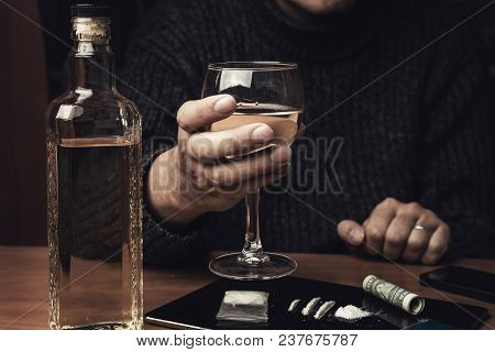 Man holds glass of whiskey and uses cocaine drugs. Drug abuse and alcoholism concept, toned stock photo