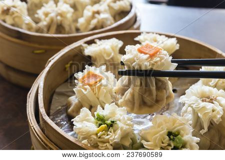 Enjoying traditional Chinese dumpling called Shumai at a restaurant stock photo