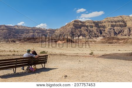 Couple of happy seniors looking at the valley of geological Timna park and dry riverbed. It is located 25 km north of Eilat (Israel), combines beautiful scenery with unique geology, variety of sport and family activities stock photo