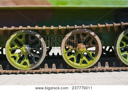 Part of a continuous track on a military amphibious vehicle. The vehicle has a verdant camouflage scheme on it. stock photo