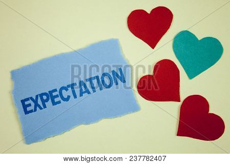 Handwriting text Expectation. Concept meaning Meteorological research analyst predicts weather forecast written Tear sticky note paper piece plain background paper Hearts next to it. stock photo