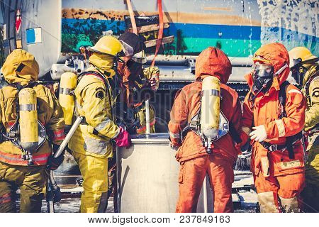 Firemen in firefighter uniform are checking their equipment. During fire drill and training for safety with foam and chemical fire suppression systems. Backside is fuel tanker truck. Vintage tone. stock photo