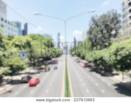 blurred image of traffic jam on the road and opposite side of the road is empty road with green environment and modern building in Bangkok, Thailand . busy road in the morning stock photo