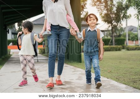 Mother And Pupil And Kids Holding Hands Going To School In First Class With Schoolbag Or Satchel Wal