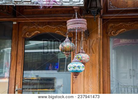 Traditional multi-colored glass Arabic lamp near the wooden front door, Turkey, Istanbul stock photo