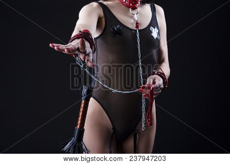BDSM Concepts and Ideas. Front View of Mature Caucasian Female with Accessories for Sado-Masochism Play. Posing with Leather Lash  Against Black. Horizontal Shot stock photo