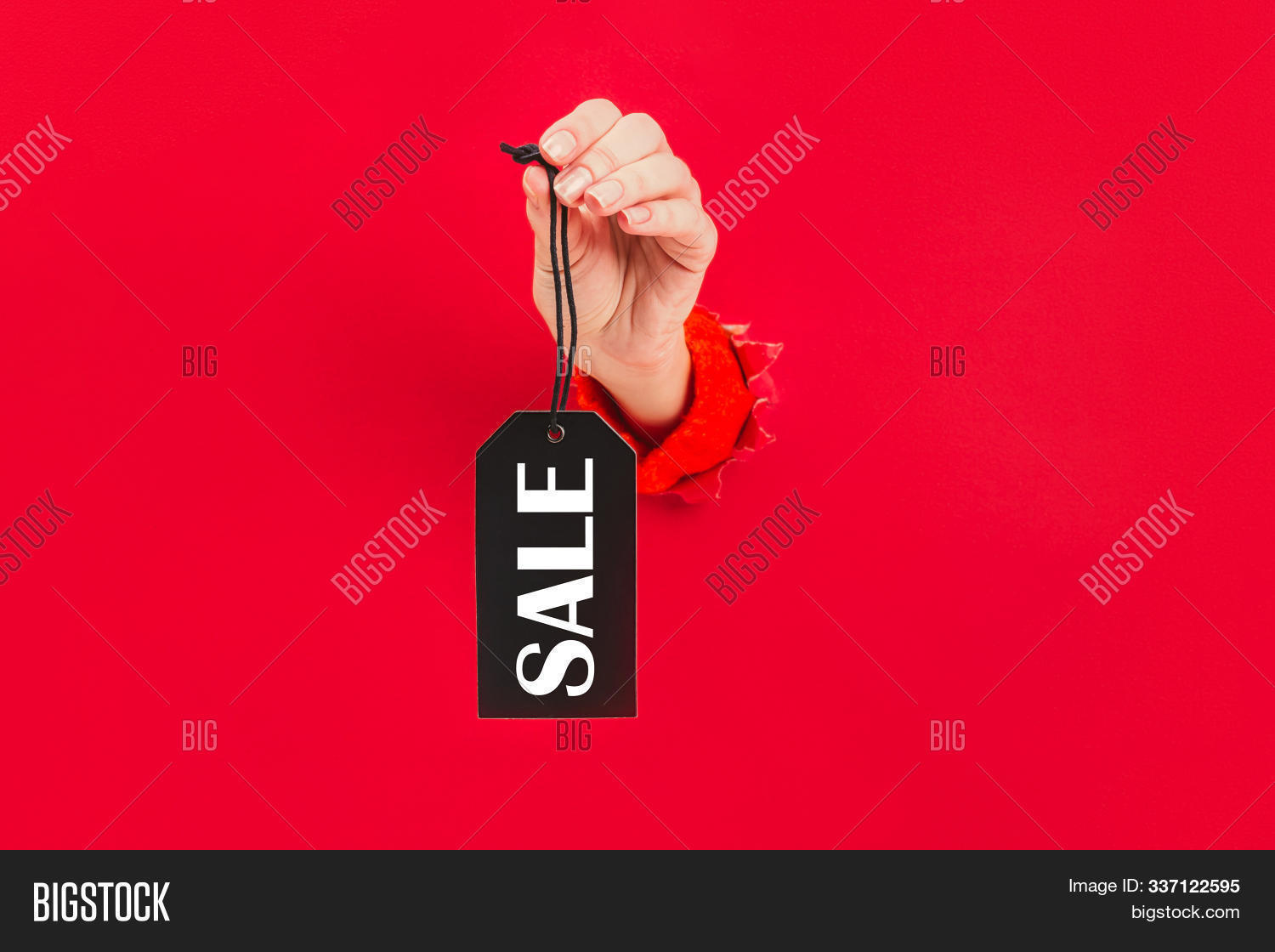 Black tag with word sale in female hand through a hole in red background. Price tag, gift tag, address label.