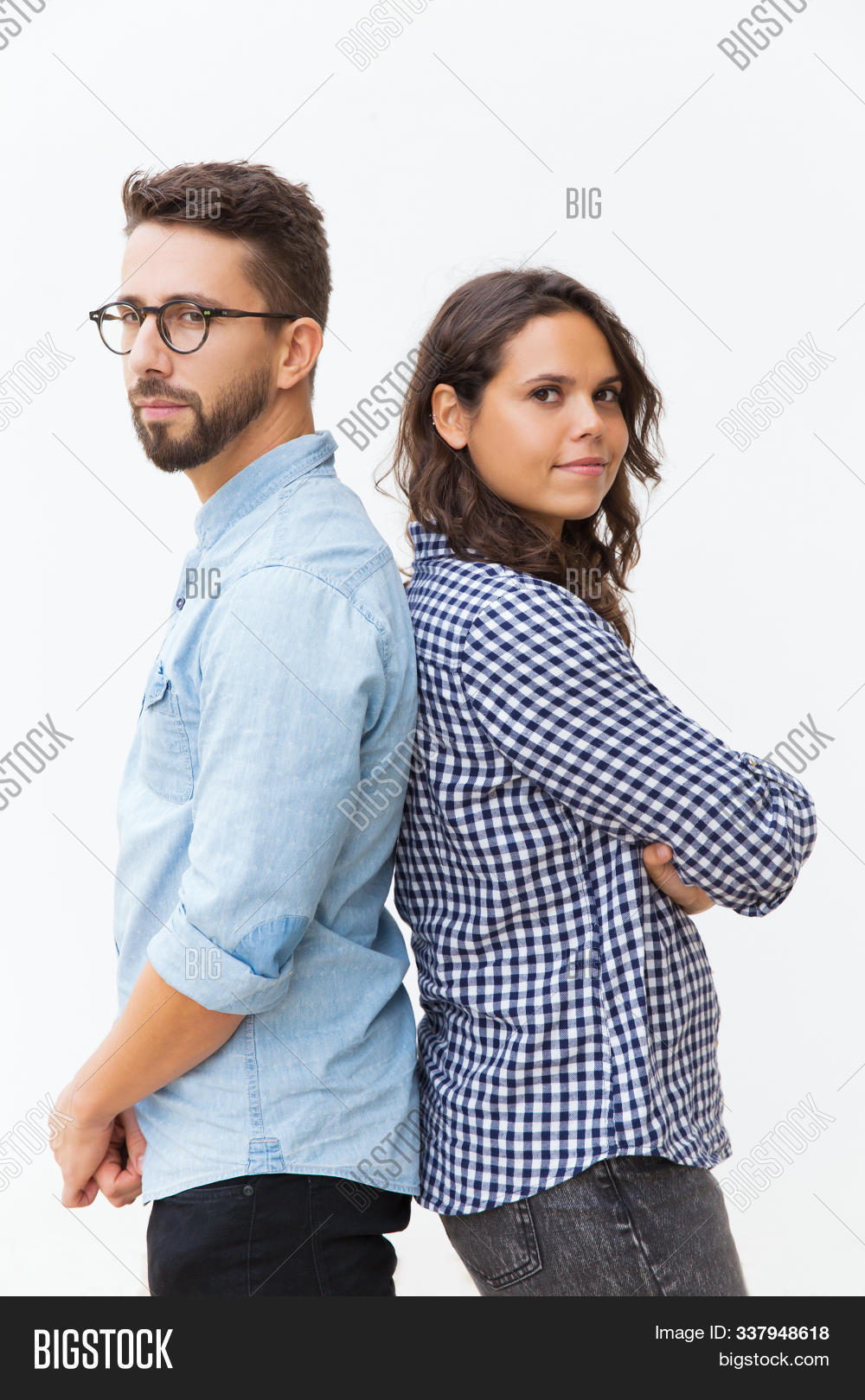 Serious pensive couple standing back-to-back, looking at camera. Young woman in casual and man in glasses in glasses posing isolated over white background. Relationship and support concept