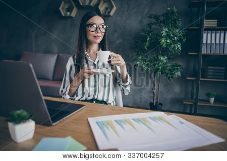 Photo of cheerful positive business woman resting with cup of tea drinking delicious beverage during break at work as financier stock photo