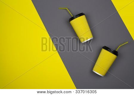 Yellow paper cup of coffee on a yellow, gray background. Aroma tasty morning hot takeaway drink, layout for coffee shop. Concept of business and services. Bright hipster design, modern abstraction. stock photo