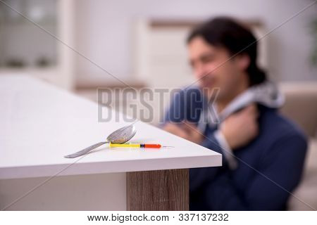 Young man having problems with narcotics at home stock photo