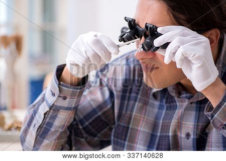 Young male jeweler at workshop stock photo