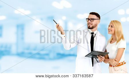Doctor with patient pointing at empty copy space for your text. The happy patient is listening to explanation from the doctor. Concept of medical healthcare and doctor staff service. stock photo