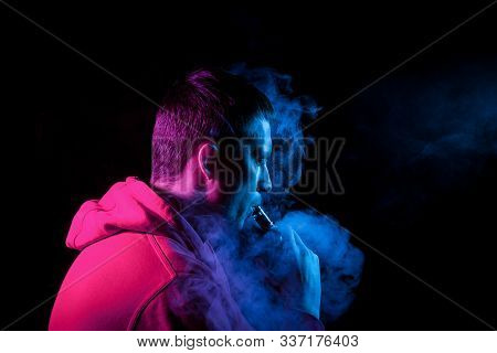 An adult brunette man holds in his hand and drags on an electronic cigarette with a vape while smoking and releases blue smoke to the sides, his face is highlighted with pink light. stock photo