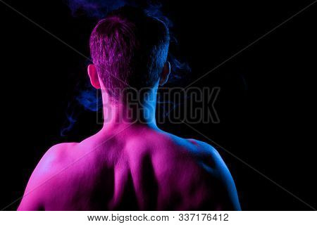 Close-up of nape, back and shoulders with strained muscles of an short hair head of a man with stubble, naked without clothes, illuminated in blue and pink on a black isolated background with smoke stock photo