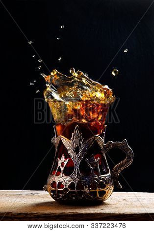 Turkish tea in the glass on the table. Eastern. Tea splashes. Splashing Turkish Tea in traditional Turkish tea glass in metal glass frame. stock photo