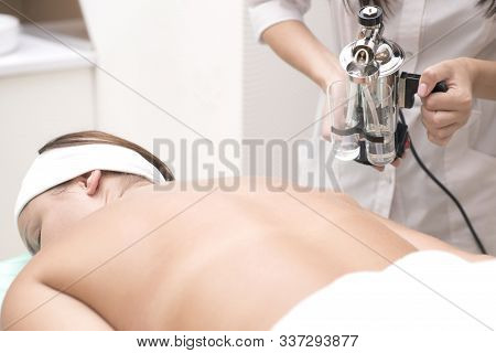 Using a device, a professional cosmetologist-masseur sprays essential oil onto the skin of the back of a young patient. Spa treatments in the beauty salon stock photo