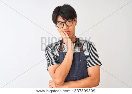 Chinese bartender man wearing apron and glasses standing over isolated white background thinking looking tired and bored with depression problems with crossed arms. stock photo
