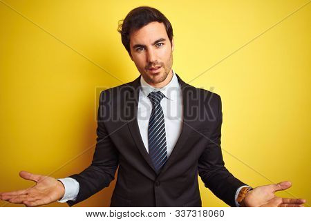 Young handsome businessman wearing suit and tie standing over isolated yellow background clueless and confused with open arms, no idea concept. stock photo